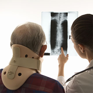 medical professional pointing at a patient's xray while explaining their neck injury