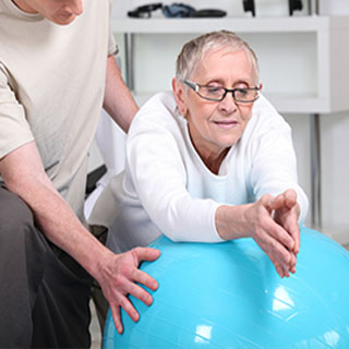 physical therpaist helping a patient balance on a ball