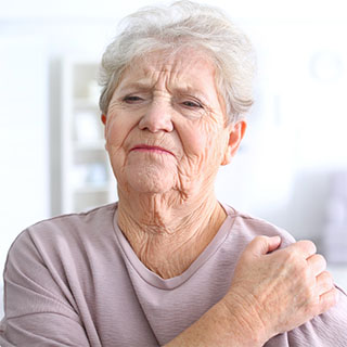 an elderly person gripping the shoulder in discomfort
